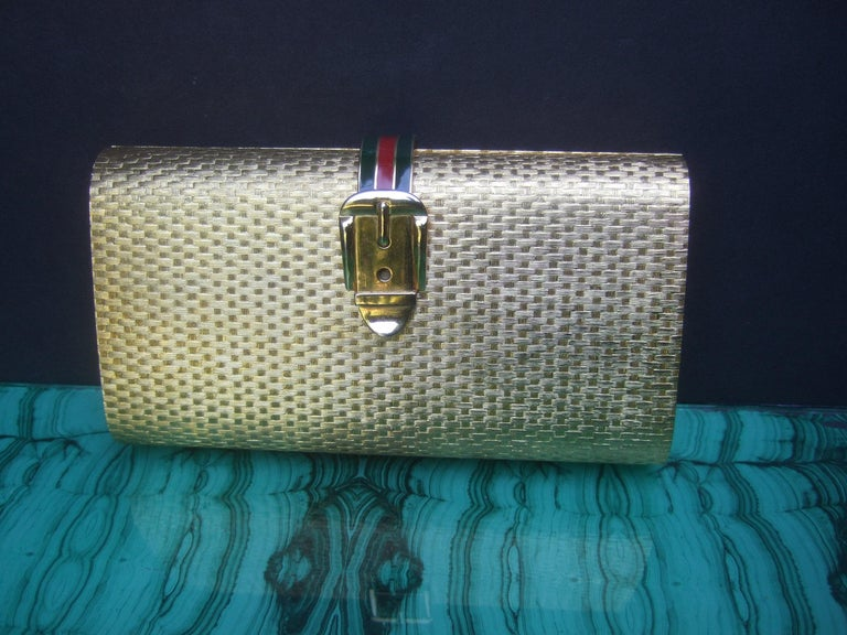 Gucci Italy Rare gilt metal minaudiere' clutch bag c 1970s The opulent gold metal clutch is designed with a contiguous textured geometric basket weave pattern throughout the exterior  Adorned with a gilt metal buckle clasp emblem; accented with