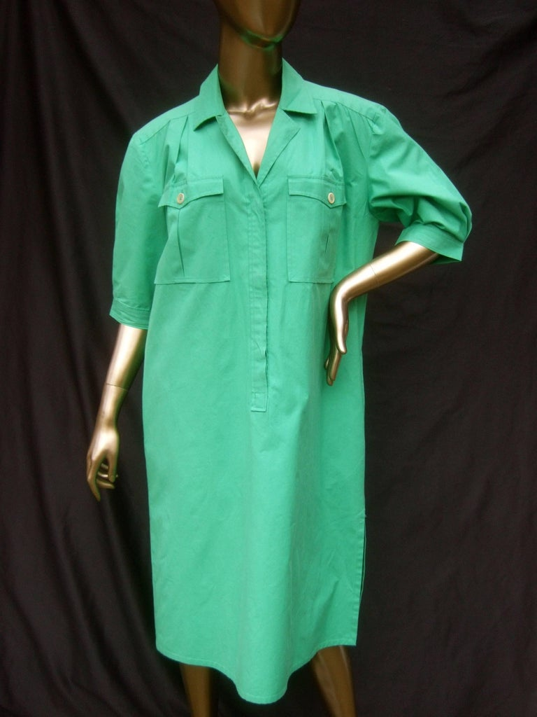 Gucci Italy Green cotton crisp shirt dress c 1970s The stylish Italian shirtdress is designed with cool cotton fabric  The front bodice has a pair of flap cover buttoned pockets. The buttons that run down the front are concealed   The shoulders,