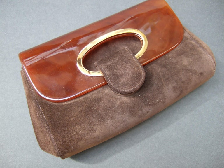 Gucci Italy Rare amber lucite brown suede clutch bag c 1970s The unique Gucci clutch is designed with a sleek amber color lucite flap cover on the front exterior. The Italian clutch is covered with plush dark chocolate brown suede  The suede covered