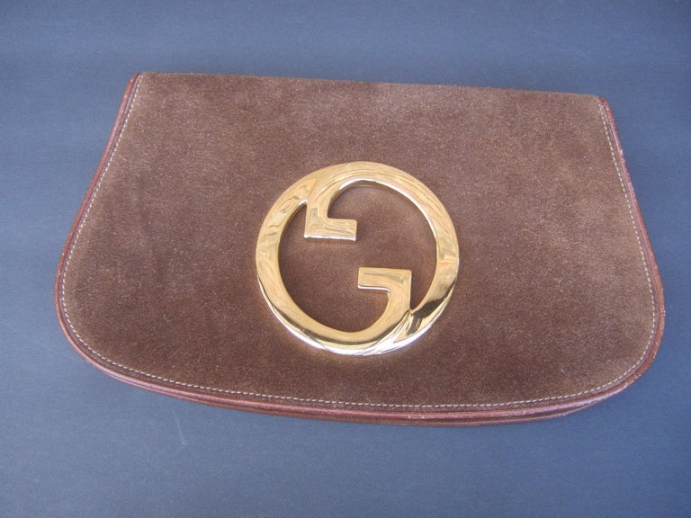 Gucci Italy Brown suede blondie clutch c 1970s The rare Gucci clutch is covered with luxurious chocolate brown suede  Adorned with Gucci's massive gilt metal interlocked  G.G. initials. The interior is lined in tan suede designed  with a slip pocket