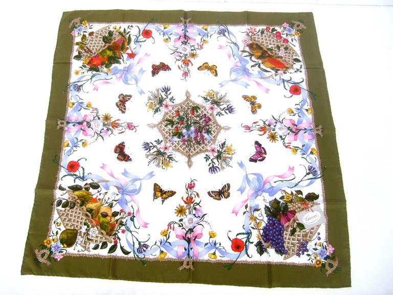 Gucci Italy Spring floral & butterfly hand rolled silk scarf c 1970s  33.5 x 34 inches  The elegant silk scarf is illustrated with a collection of fluttering butterflies circling a group strawberries, grapes and fruits   Each corner of the luxurious