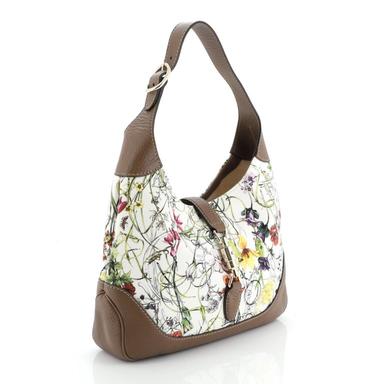 This Gucci Jackie O Bag Flora Canvas Small is a classic piece with its pattern inspired by a personal request by Grace Kelly in 1966. Crafted in white printed canvas, it features an adjustable shoulder strap and gold-tone hardware. Its piston lock