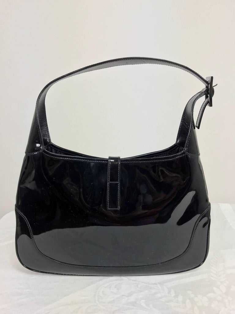 Gucci Jackie O black patent leather handbag...Always stylish this patent leather Gucci bag has silver hardware and is lined black Gucci logo fabric...Shoulder bag...In excellent condition with light wear... Measurements are in inches: 13 wide at