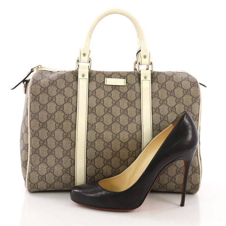 86948cd758c3 This Gucci Joy Boston Bag GG Coated Canvas Medium, crafted in brown GG  coated canvas