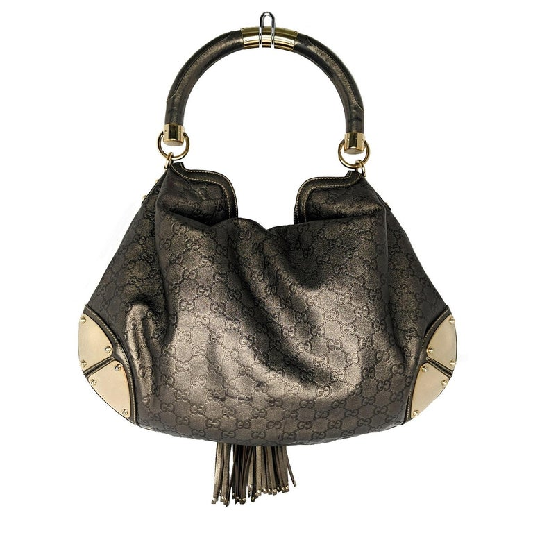 We can always count on Gucci for styles that we love now and later. This gorgeous Gucci Metallic Bronze Guccissima Leather Large Babouska Indy Top Handle Bag features a chic hobo design with a top handle with a gold-tone Gucci logo, dual bamboo