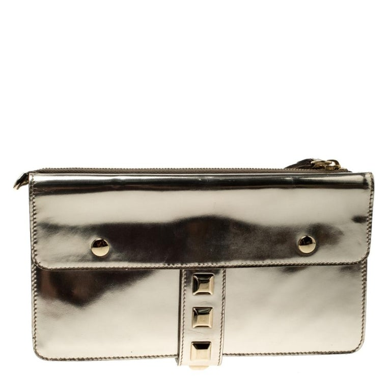 Crafted from light gold patent leather and styled with gold-tone studs to the front, this Gucci evening wristlet is that handy accessory that you'll love to carry for parties and evening outings. It features two buckled flap pockets on the front