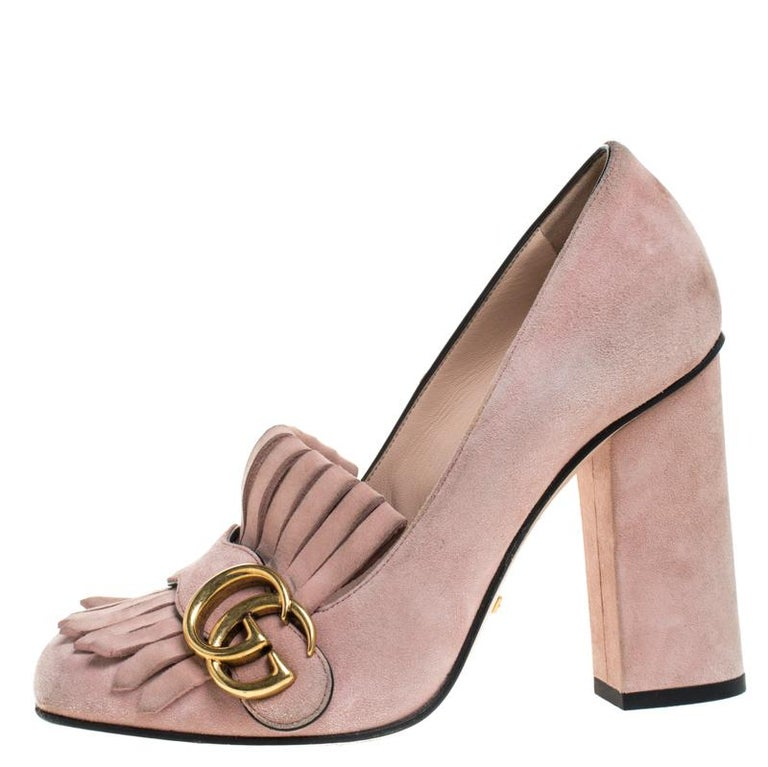 Pretty and easy to flaunt, this pair of Marmont pumps by Gucci is a stunner. They've been crafted from light pink suede and styled with folded fringes with the brand's signature GG on the uppers. Square toes, block heels and sturdy leather soles