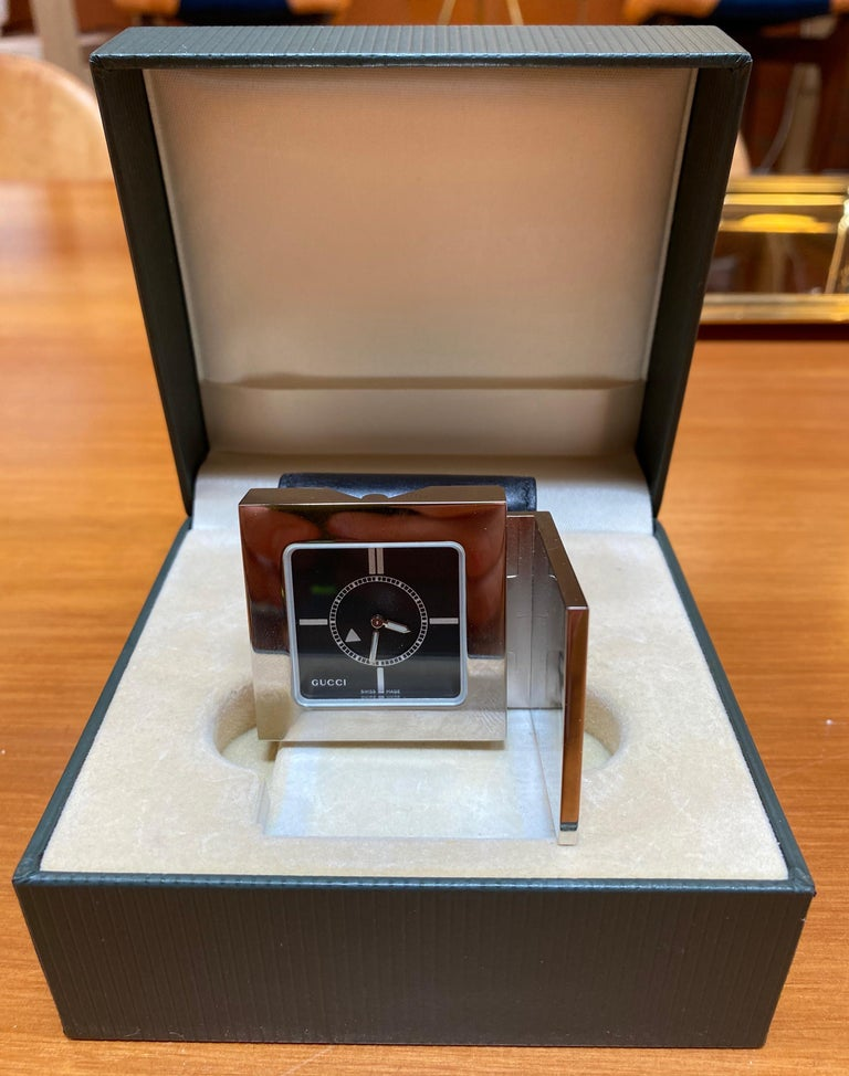 Rare authentic Gucci deluxe chrome cased pocket size, alarm travel clock watch that folds out to stand. Alarm indication on rotation, number 3895 engraved on back, model 0895, Swiss made quartz movement. Comes in soft leather calfskin pouch with