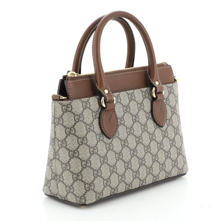 This Gucci Linea A Convertible Tote GG Coated Canvas Mini, crafted in brown GG coated canvas, features dual rolled leather handles, protective base studs, and gold-tone hardware. Its zip closure opens to a brown microfiber interior with slip