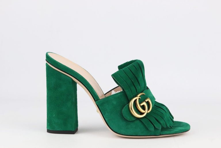 Gucci's 'Marmont' shoes are coveted by fashion influencers, editors and celebrities alike, made in Italy from smooth green suede, these mules are detailed with heritage kiltie fringing and the house's iconic burnished 'GG' plaque.  Soles measures