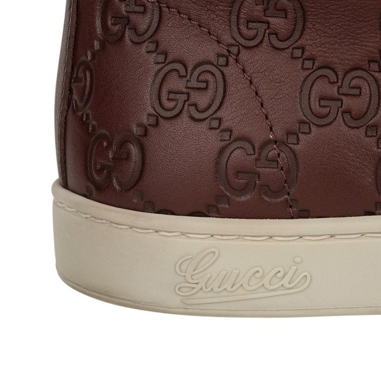 Guaranteed authentic Gucci mens high top sneakers. Burgundy logo embossed high top leather sneaker. Grosgrain ribbon in chardonnay and green along sides. Gucci logo on edge. Some wear on soles.  See images. Comes with signature box and