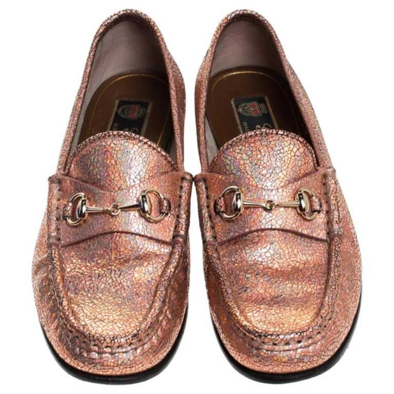 These Gucci loafers are a must-have. Crafted from textured leather, they come in a stunning shade of metallic bronze. They make a complete statement and feature the brand's signature Horsebit detail on the uppers. You can easily slip them on and