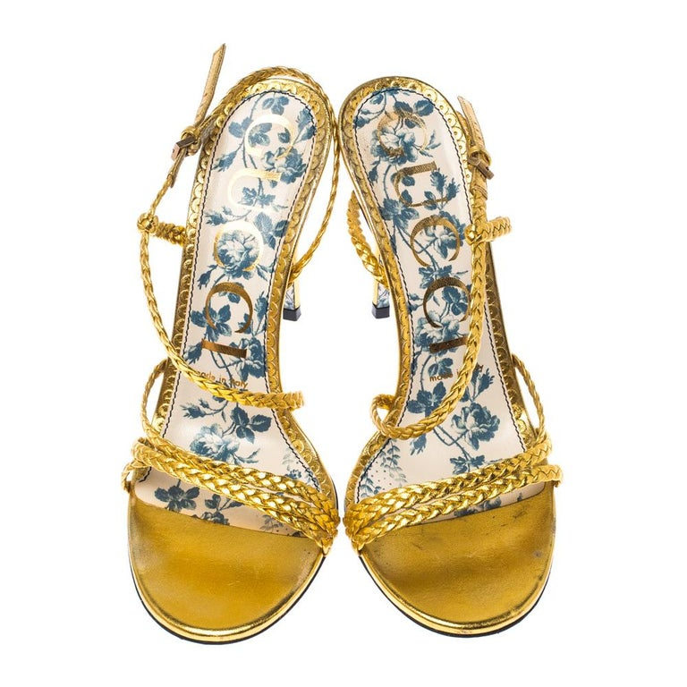 Beauty flows out of these sandals from Gucci! Crafted from metallic gold leather, these sandals are enchanting. They feature a design of braided straps across the toes and as slingbacks. The sandals are complete with floral-printed soles and 10.5 cm