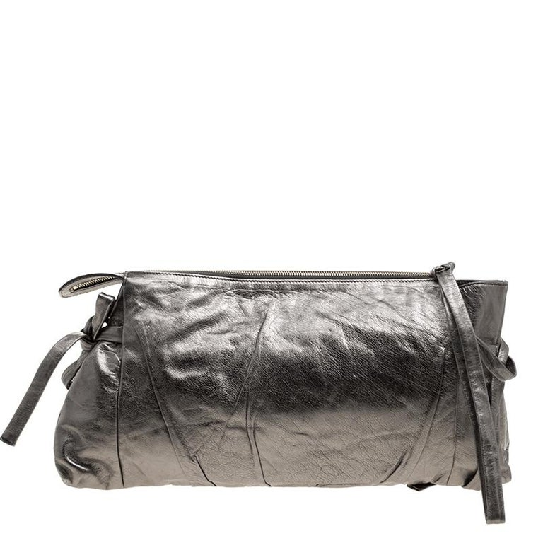 This Gucci clutch is built to suit your stylish ensembles. Crafted from leather, it has a metallic grey shade and a zipper which secures a nylon interior. The clutch is complete with the signature Hysteria emblem on the front and a wristlet.