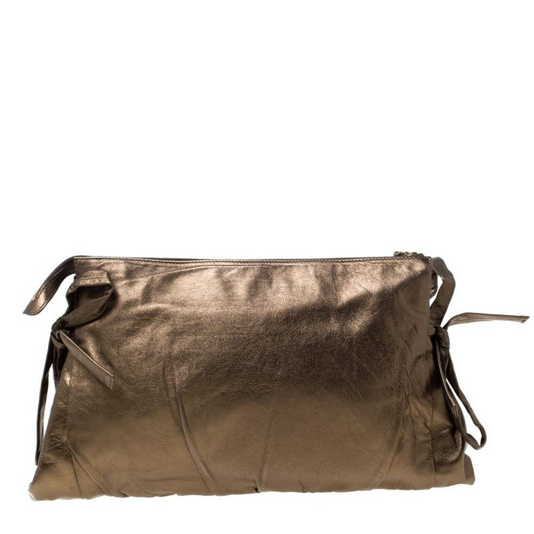 This Gucci clutch is built to suit your stylish ensembles. Crafted from leather, it has a metallic olive shade and a zipper which secures a nylon interior. The clutch is complete with the signature Hysteria emblem on the front and a