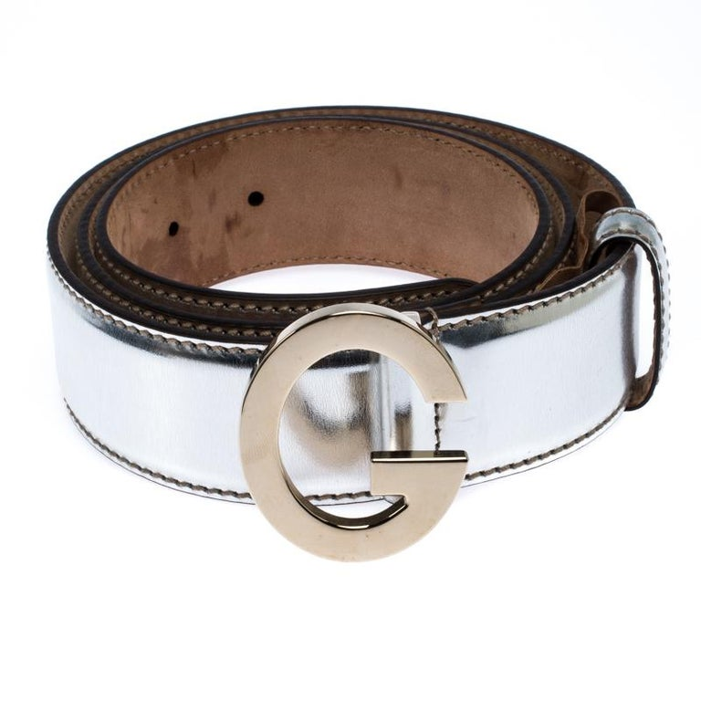 Add a luxurious touch to your accessory collection with this metallic buckle belt from Gucci. It comes made from patent leather and designed with a G buckle made from gold-tone metal. Grab it right away!  Includes: The Luxury Closet Packaging