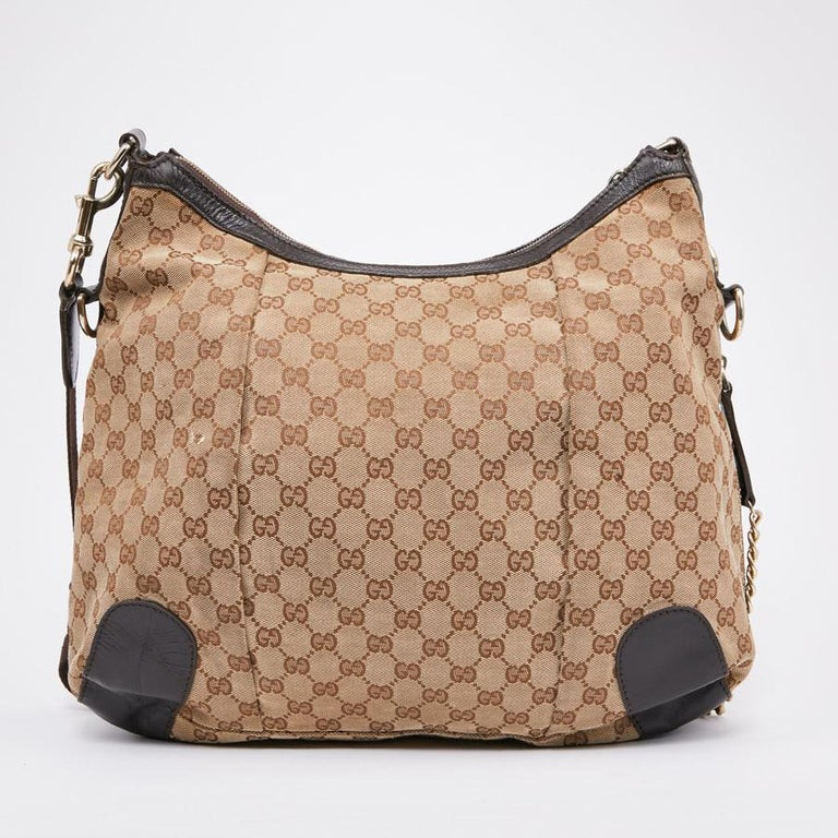 This second-hand GUCCI bag is in beige and brown monogram canvas. It has a zipper. The jewelry is in pale gold gold metal. It can be worn with a shoulder strap or crossed. The interior is in brown fabric with a zipped pocket and two patch pockets.