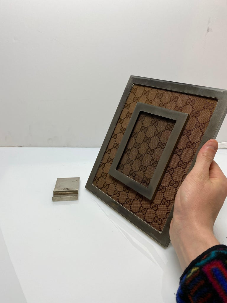 A Classic and iconic picture frame from Gucci. Featuring their monogram canvas as a mat for the picture. It is marked Gucci on the base of the stand. The frame itself can be lifted off the Stand to appreciate in the hand as well.  Fits a 3