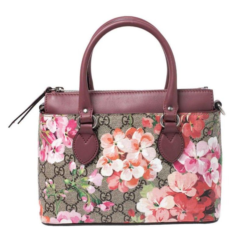 This chic bag from Gucci will enhance both your casual and evening wear. Crafted with GG Supreme canvas and leather, the bag features beautiful florals, dual handles, and a detachable shoulder strap. The bag is equipped with a top zip closure that