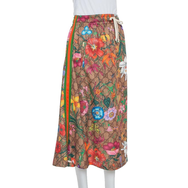 Make room in your closet for this creation from the house of Gucci. Designed for a fashionable look, this midi skirt is covered with flora prints over the brand's signature monogram. This skirt has a flared shape and an elasticized