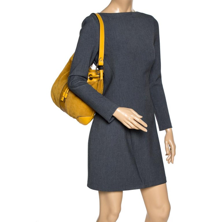Beautifully designed and lovely to look at, this hobo will perfectly complement your feminine attires. The bag is crafted with mustard-colored suede and leather and detailed with Guccissima trim at the centre. It features a drawstring fastening, a