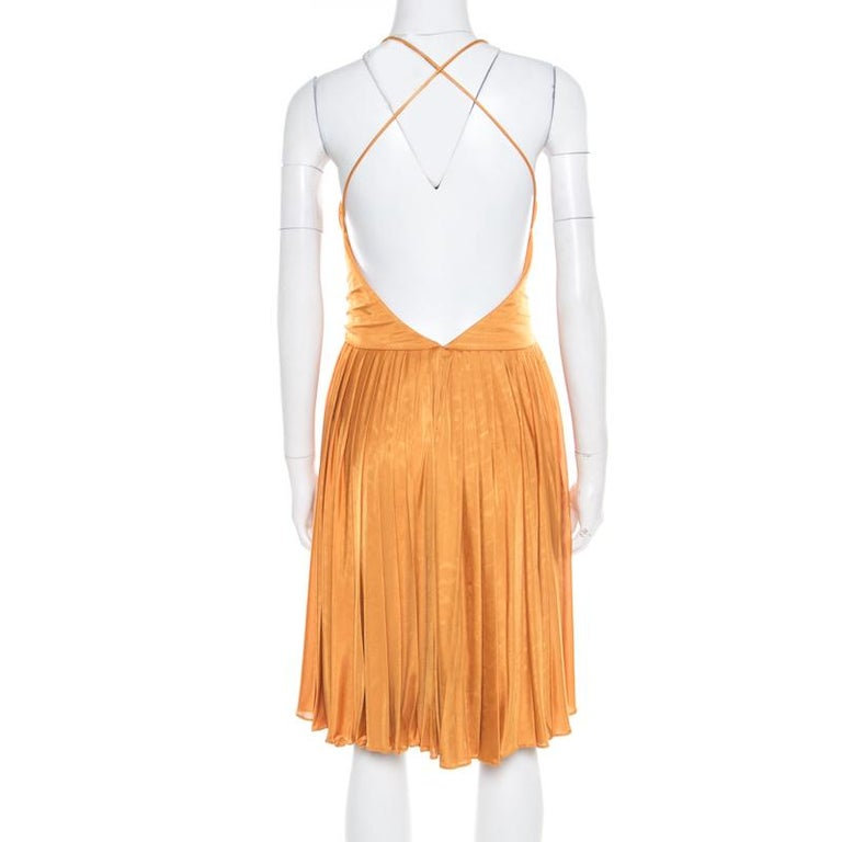 We've fallen in love with this gorgeous dress from Gucci! Vibrant in mustard yellow, this creation features a plisse silhouette and flaunts a plunging neckline and a deep cut-out back that looks amazing. Pair it with platform sandals and an