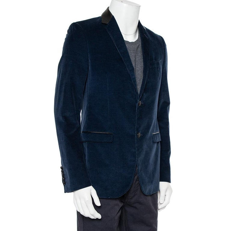 This men's blazer from Gucci is sure to make you look your best from every angle. The navy blue corduroy blazer features three pockets, leather trims and a button front closure.