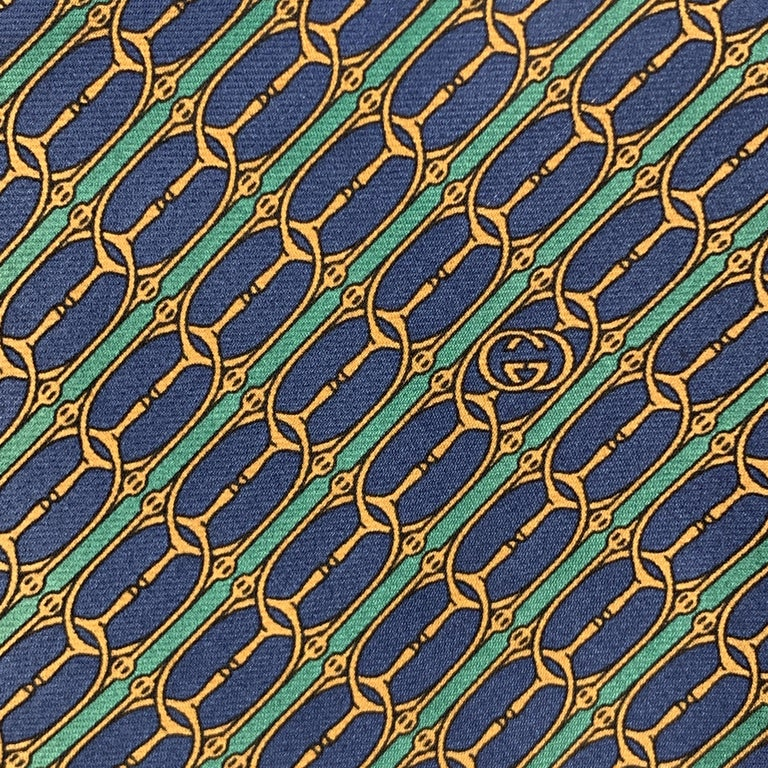 Vintage GUCCI necktie comes in navy & green striped silk twill with all over gold horsebit print. Made in Italy.  Excellent Pre-Owned Condition.   Width: 3.75 in.