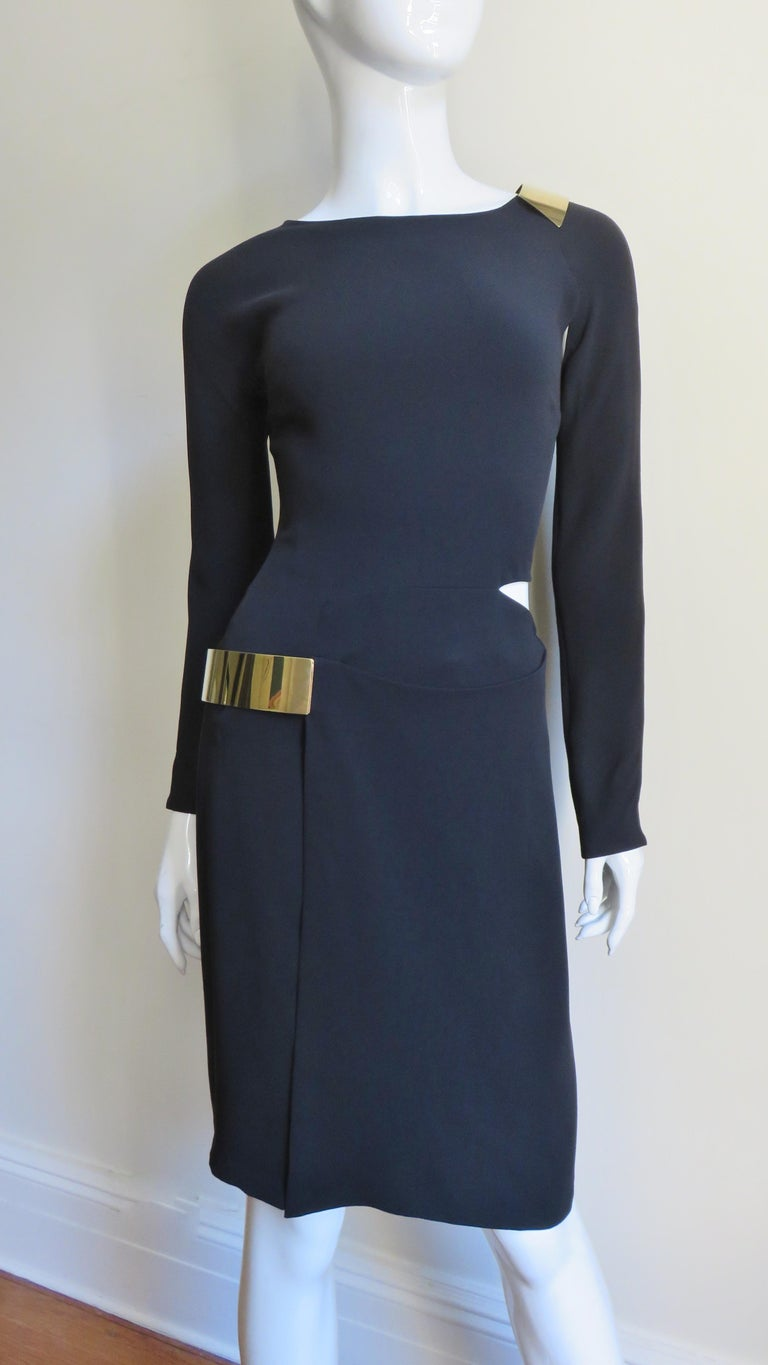A fabulous black silk jersey dress from Tom ford for Gucci.  It has a simple neckline, long zipper sleeves and cut outs at a shoulder and side waist plus a front slit in the straight skirt..  The skirt slit and shoulder cut out are highlighted with