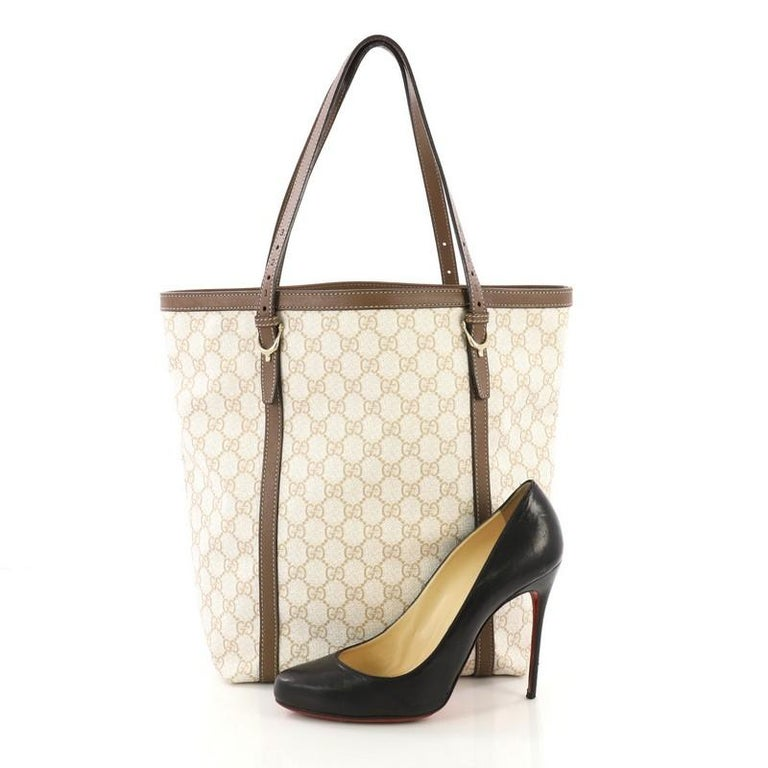 This Gucci Nice Tote GG Coated Canvas Tall, crafted in off-white GG coated canvas, features dual adjustable flat handles with spur details, brown leather trims, and gold-tone hardware. Its middle hook closure opens to a white canvas interior with