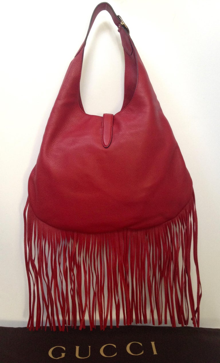 Gucci Nouveau fringe leather hobo handbag.  Red leather with silver piston closure and adjustable buckled shoulder strap with 9