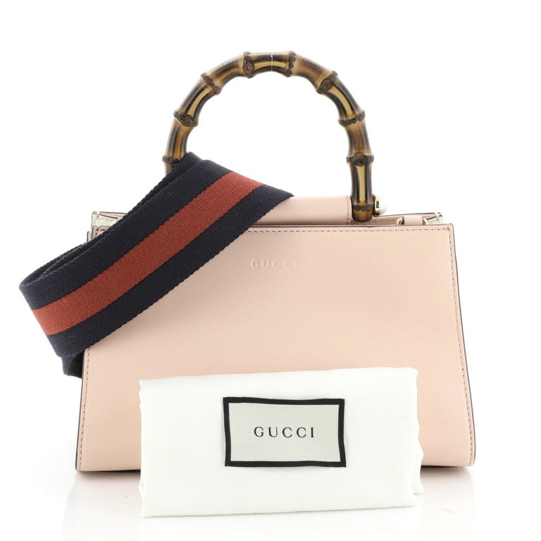 This Gucci Nymphaea Top Handle Bag Leather Mini, crafted in pink leather, features a bamboo handle with pearls and gold-tone hardware. Its magnetic snap closure opens to a gray microfiber interior with zip and slip pockets. These are professional
