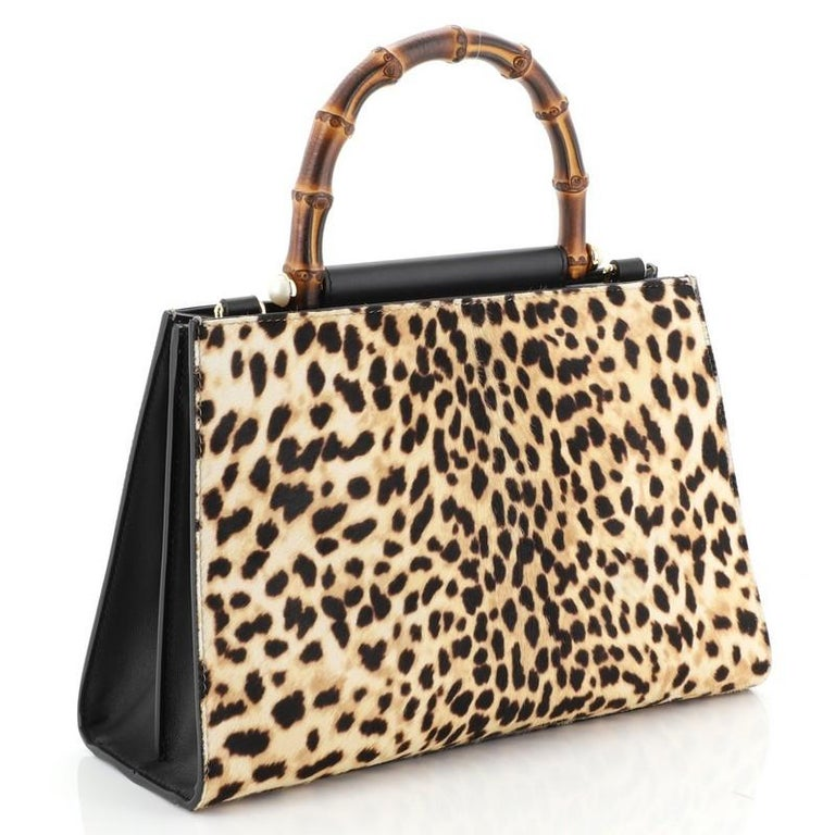 This Gucci Nymphaea Top Handle Bag Printed Calf Hair Small, crafted in brown printed calf hair, features a bamboo top handle and gold-tone hardware. Its magnetic snap closure opens to a neutral microfiber interior with zip and slip pockets.