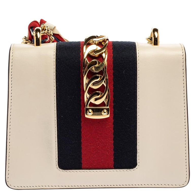 From the house of Gucci comes this gorgeous Sylvie shoulder bag that will perfectly complement all your outfits. It has been luxuriously crafted from off white leather and styled with a chain-web decorated flap and a gold-tone buckle lock to secure