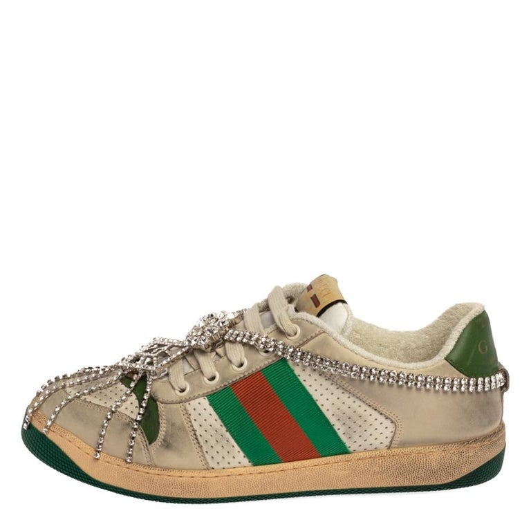 This pair of Screener sneakers by Gucci has been treated for a vintage, distressed effect. They are crafted from leather and feature the famous Web trim, the iconic GG logo, and lace-up vamps adorned with crystals. The low-top shoe is made in