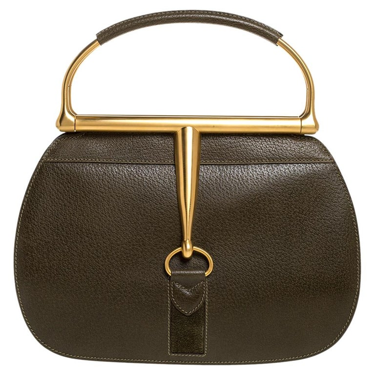 This vintage piece manifests Gucci's take on the doctor's bag. It features the distinctive Horsebit accent on the front as well as back for a signature look. It's polished green leather exterior is framed beautifully with a gold-tone top and metal