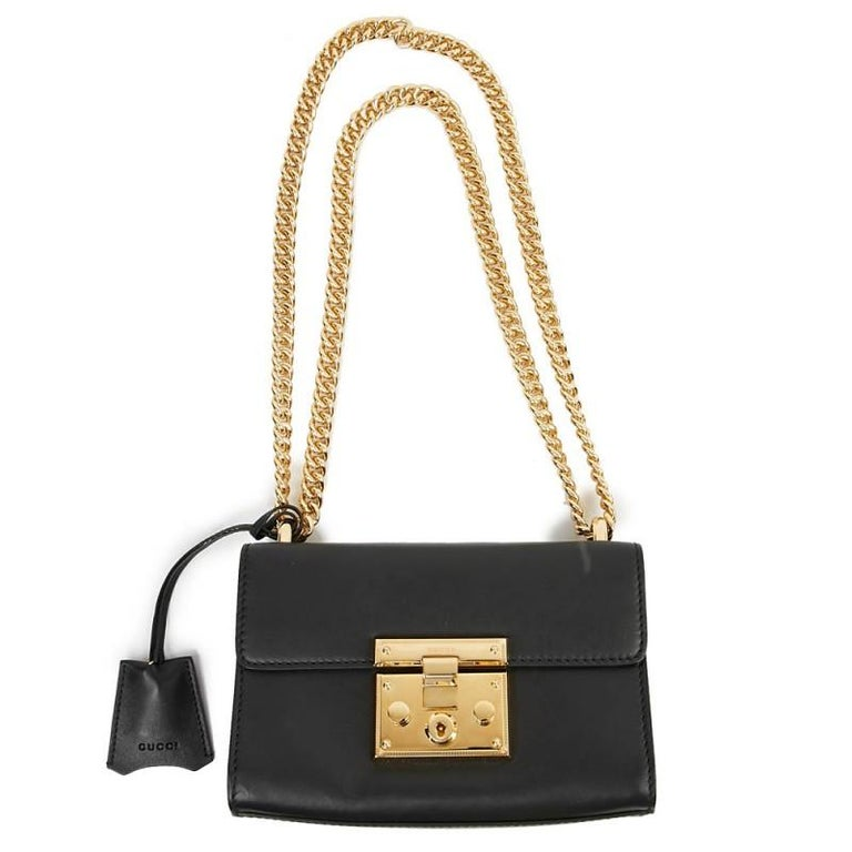 Season after season, the Padlock bag from GUCCI has new designs, sizes, colors or leathers. It has became an iconic bag for the brand. This one is in smooth black leather with gilt metal jewelry. It is lined in camel suede-style leather and