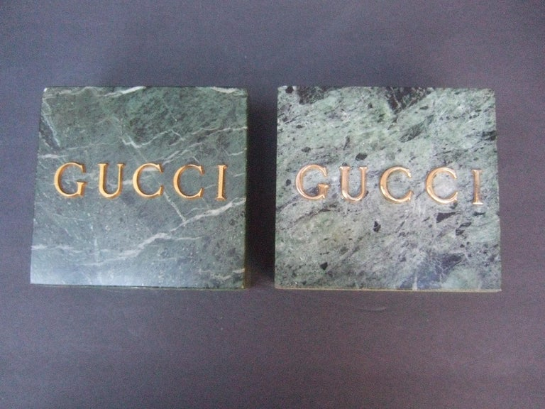 Gucci pair of muted green marble stone bookends / decorative objects c 1970s The sleek pair of green marble blocks were originally display fixtures at Gucci boutiques in the 1970s and 1980s  The pair of Gucci inscribed marble blocks could be