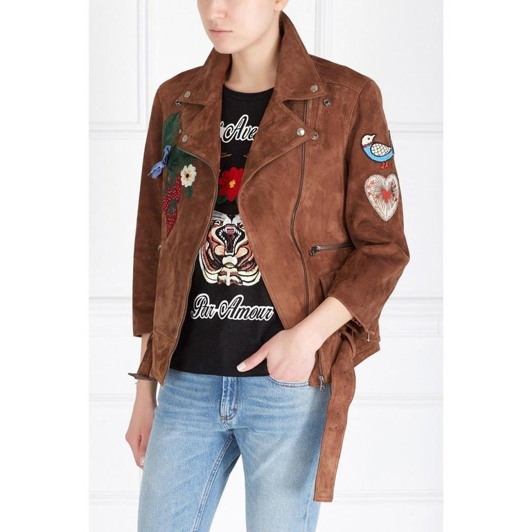 This leather bomber jacket is embellished with embroidered flower appliques, a large bee, a signature detail for the brand.  Across the back reads the phrase