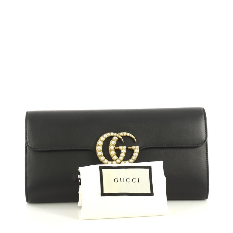 This Gucci Pearly GG Marmont Clutch Leather, crafted from black leather, features pearl studded GG logo and aged gold-tone hardware. Its magnetic closure opens to a brown leather interior with slip pocket.   Estimated Retail Price: $1,100 Condition:
