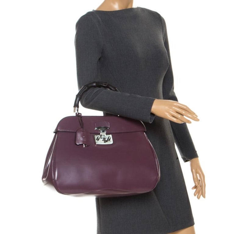 Featuring the iconic Lady Lock, this top handle bag is from Gucci. This bag is crafted from purple patent leather and features a bamboo top handle. The push lock closure opens to a suede-lined interior that houses two open compartments. Carry this