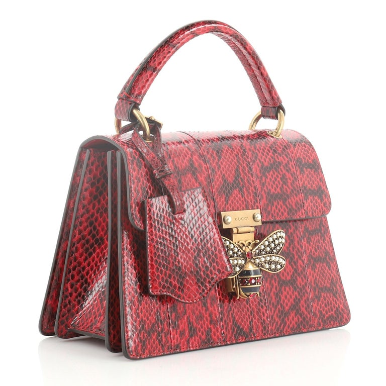 This Gucci Queen Margaret Top Handle Bag Snakeskin Small, crafted from genuine red snakeskin, features a leather top handle, bejeweled bee on its flap, and aged gold-tone hardware. It opens to a blue microfiber interior with three compartments and
