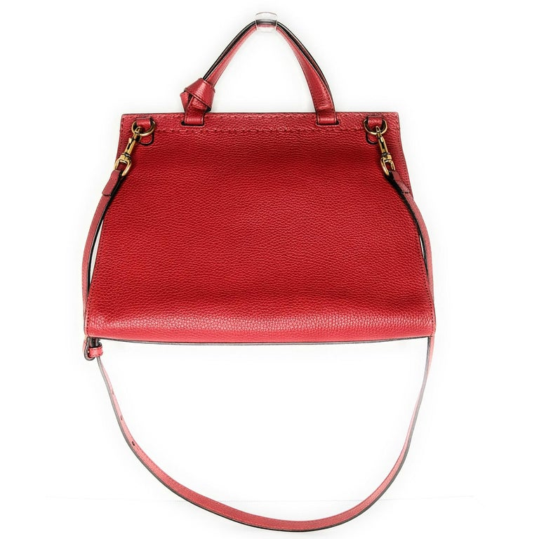 Red grained leather Gucci handle bag with antiqued gold-tone hardware, single flat top handle, creme canvas lining, three pockets at interior walls; one with zip closure and push-lock closure featuring GG Marmont adornment at front flap. Retail
