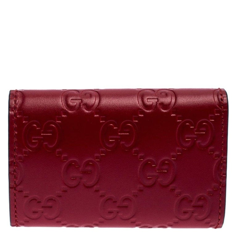 Stylish and functional, this Gucci key holder is a handy creation. Crafted from red Guccissima leather, it has the capacity to hold six keys inside. Its classic design is enhanced by gold-tone hardware and a bow on the front.  Includes: Info