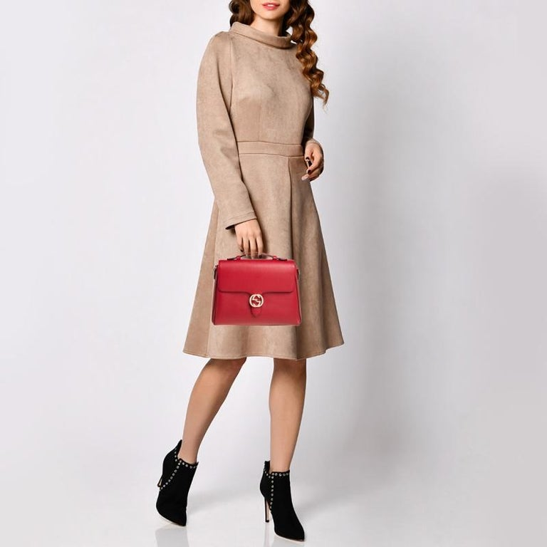 This Gucci top handle bag is a minimal design that exhibits sophistication. Crafted from red leather, it features a structured silhouette adorned with a logo accented front flap that opens to a well-sized interior. Hold it by the top handle and