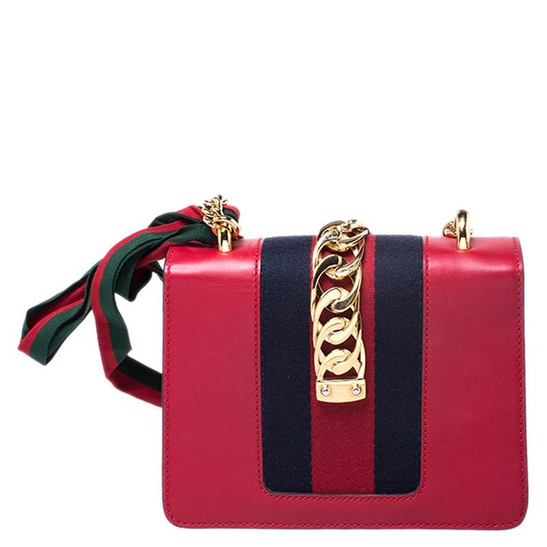 From the house of Gucci comes this gorgeous Sylvie shoulder bag that will perfectly complement all your outfits. It has been luxuriously crafted in Italy and is made from red leather and styled with a signature chain-web decorated flap, a buckle