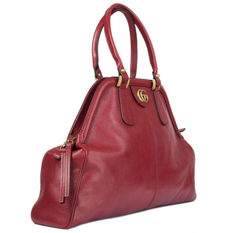Gucci 'Re (Belle) Small' shoulder bag in red supple natural grain leather with a washed and brushed finish. Opens with a double zipper on top and is lined in light pink microfibre with one zipper pocket against back and one against the front. The GG