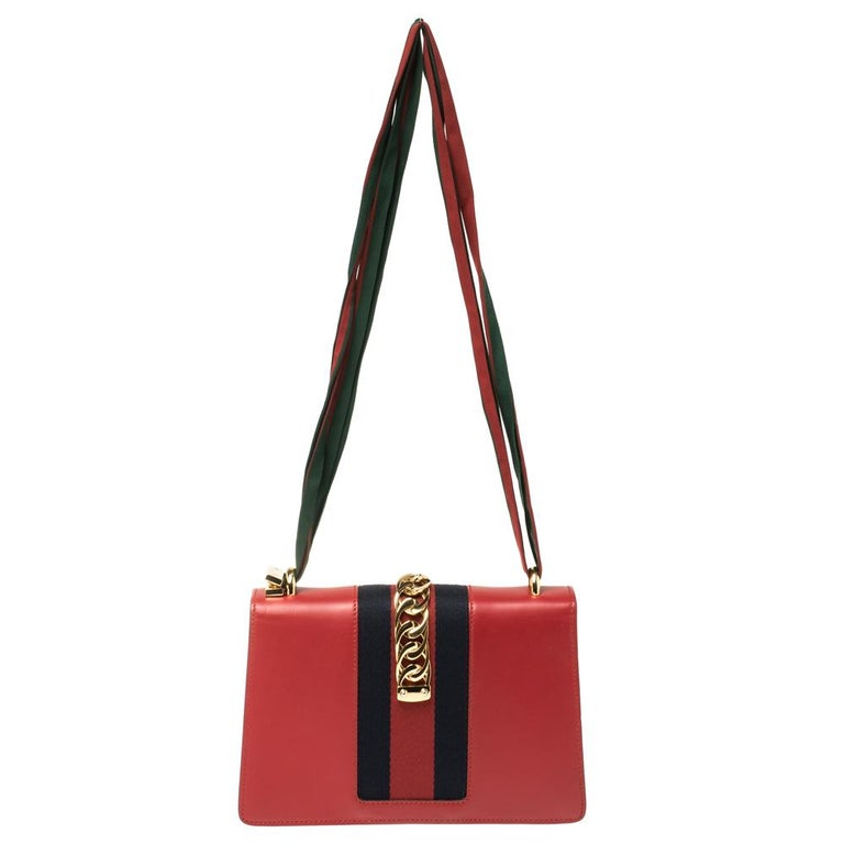 From the house of Gucci comes this gorgeous Sylvie shoulder bag that will perfectly complement all your outfits. It has been luxuriously crafted from red leather and styled with a chain-web decorated flap and a buckle lock to secure the suede