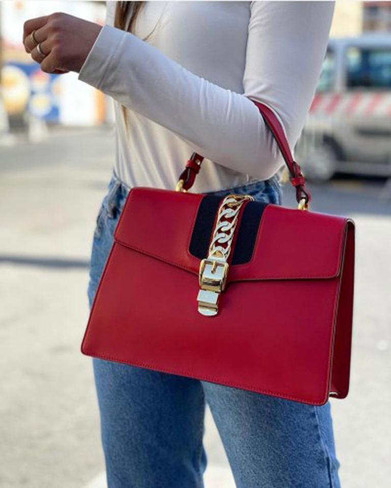 Gucci Sylvie line bag made of red leather with golden hardware. Hook closure, very large inside. Equipped with top handle and removable shoulder strap. The bag is in good condition.  Dimensions: 19 × 31 × 30 cm