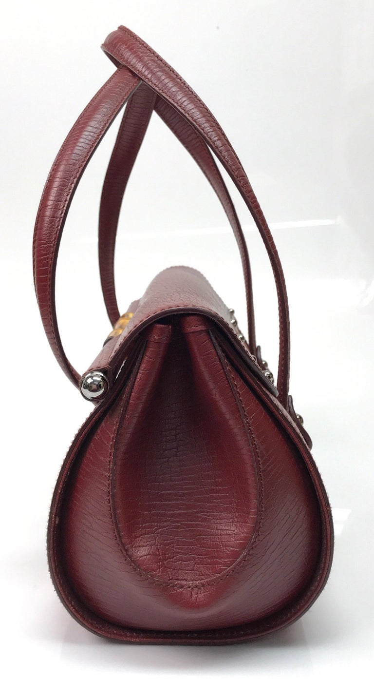 Gucci Red Monogram Leather Bamboo Bullet Handbag. This stunning Gucci handbag is in great condition. It has minimal sign of use that is consistent with age. There are small markings on the leather and the front silver buckle has minor scratches. The